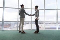 两个商人震动手协议Coworking中心企业队工友在前面大全景窗口里站立 库存照片