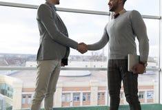 两个商人震动手协议Coworking中心企业队工友在前面大全景窗口里站立 图库摄影