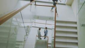 两个商人顶视图见面在现代办公室中心和谈话的楼梯,当女性同事走的台阶时