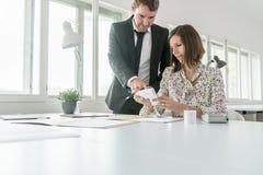 两个商务伙伴男人和妇女计算的费用和 库存图片