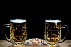 两个啤酒杯和开心果反对黑背景 库存照片