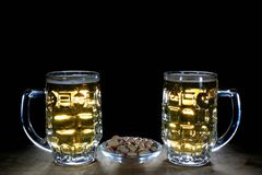 两个啤酒杯和开心果反对黑背景 免版税库存照片