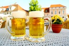 两个啤酒杯啤酒庭院在城市 库存图片