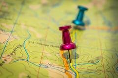 两个图钉变粉红色和在绿色地图埋置的蓝色 库存图片