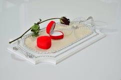 两个圆环箱子和一朵玫瑰在盘子。 免版税库存图片