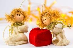 两个圣诞节天使和红色天鹅绒心脏在白色背景 图库摄影