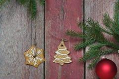 两个圣诞节曲奇饼从红色木墙壁,与圣诞节装饰的冷杉分支垂悬 库存图片