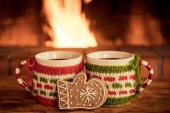 两个圣诞节杯子在壁炉附近的被仔细考虑的酒 免版税库存照片