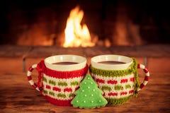 两个圣诞节杯子在壁炉附近的被仔细考虑的酒 库存图片