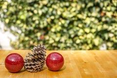 两个圣诞节球和一pinecone在一张木桌上 库存照片