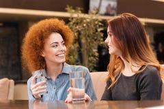 两个在咖啡馆的愉快的有吸引力的少妇饮用水 免版税库存图片