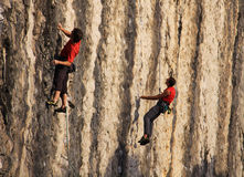 两个在垂直的石墙上的登山人实践的登山 免版税库存图片