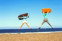 两个在大西洋夏天海滩的跳跃的孩子兴奋 免版税库存图片