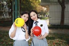 两个在学校最好的朋友的可爱的亚洲中国俏丽的女孩穿戴学生衣服微笑笑打击气球本质上 免版税库存照片