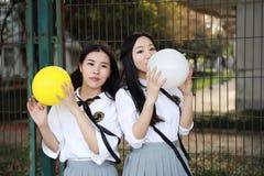两个在学校最好的朋友的可爱的亚洲中国俏丽的女孩穿戴学生衣服微笑笑打击气球本质上 免版税库存图片