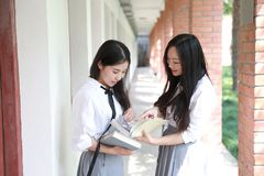 两个在学校最好的朋友的可爱的亚洲中国俏丽的女孩穿戴学生衣服微笑笑阅读书本质上 图库摄影