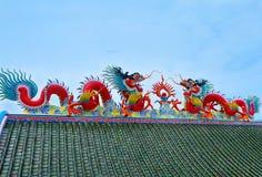 两个在屋顶寺庙的剪影中国龙有蓝天的 库存图片