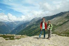 两个在岩石顶部的微笑的男孩立场 库存照片