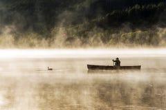两个在水的河独木舟独木舟有雾的水日出雾金黄小时Canada安大略湖在阿尔根金族国家公园 免版税图库摄影