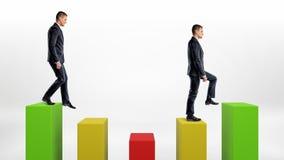 两个在白色背景的提高的商人和下来绿色,黄色和绿色统计专栏 免版税图库摄影
