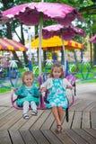 两个在的一点时尚可爱的姐妹乘驾 图库摄影