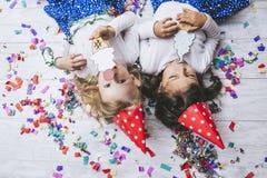 两个在的地板上的小女孩儿童时尚五颜六色的五彩纸屑 免版税库存图片