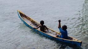 两个地方男孩剪影一条小船的在王侯的Ampat,西部巴布亚,印度尼西亚Arborek海岛上,在著名女用披巾附近 库存照片