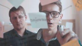 两个地道人看关于一个被日光照射了委员会的许多五颜六色的笔记自白天 工作在任务计划办公室 股票视频