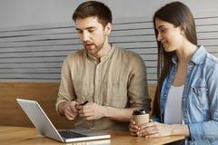 两个坐在咖啡馆,饮用的咖啡的年轻人透视起始的热心者谈论工作和看通过项目 免版税图库摄影