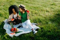 两个多种族女朋友野餐画象  他们笑,当观看事滑稽在手机和时 免版税库存图片