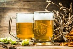 两个大啤酒杯在木桌上的啤酒特写镜头 图库摄影