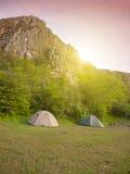 两个大帐篷参加了在山附近的森林  免版税库存图片