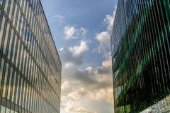 两个大现代大厦站立接近彼此,关闭天空 库存照片
