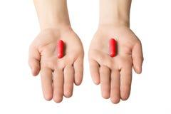 给两个大红色药片的人手 做您的挑选概念 励磁和肾上腺素 库存图片