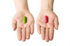 给两个大药片的人手 绿色红色 做您的选择 健康生活方式或恶习 选择您的边 库存照片