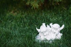 两个天使小白色小雕象在草的 免版税库存照片