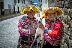 两个夫人和母羊在传统印加服装穿戴了 免版税库存图片