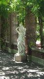 两个夫人雕象在庭院-与通过发光的阳光的树荫里 免版税图库摄影