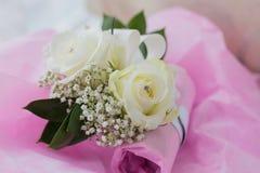 两个女傧相一张色的宏观照片'开花有一假金刚石的镯子在两朵白玫瑰的中心 免版税库存图片