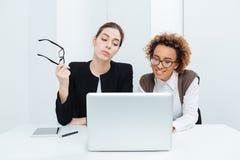 两个女商人一起坐和与膝上型计算机一起使用 免版税库存照片