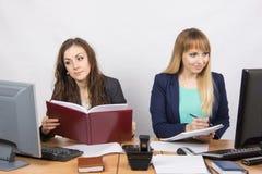 两个女商人与一个敌手桌面一起使用 库存图片