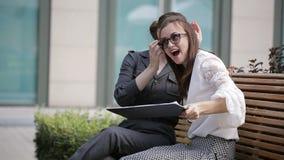 两个女商人在商业中心附近享受在长凳的一种成功的交易 股票视频