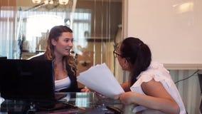 两个女商人是愉快投掷文件,并且拍他们的手在他们中的一个以后报告了好消息 影视素材