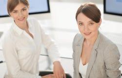 两个女商人画象工作场所的背景的 免版税库存照片
