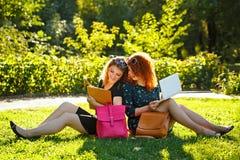 两个女学生在膝上型计算机坐草坪并且看 图库摄影