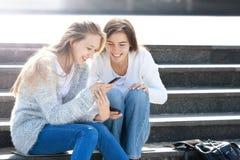 两个女孩一起谈话在街道 库存图片