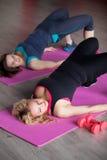 两个女孩做在席子的有氧运动锻炼在健身中心 库存图片
