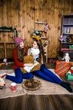 两个女孩公司有礼物的在有木墙壁的屋子里 免版税图库摄影