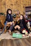 两个女孩公司有礼物的在有木墙壁的屋子里 库存图片