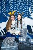 两个女孩公司蓝色和白色圣诞节装饰的 图库摄影